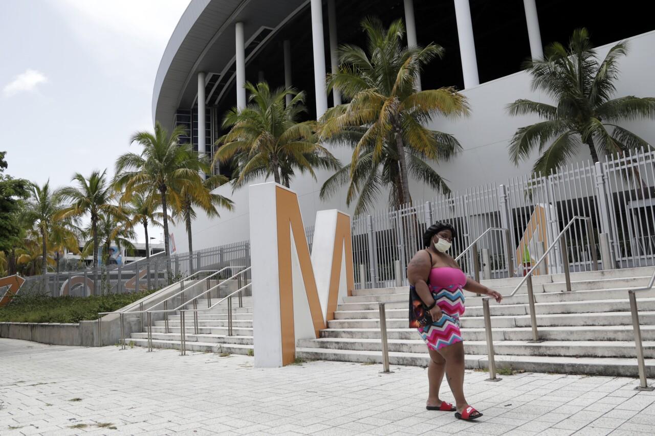 Woman wearing mask walks by empty Marlins Park, July 2020