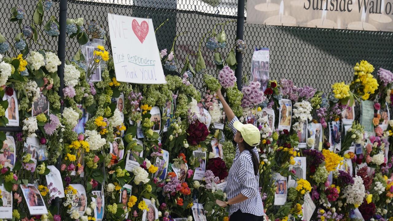 Volunteer replaces flowers at Surfside Wall of Hope & Memorial, July 1, 2021