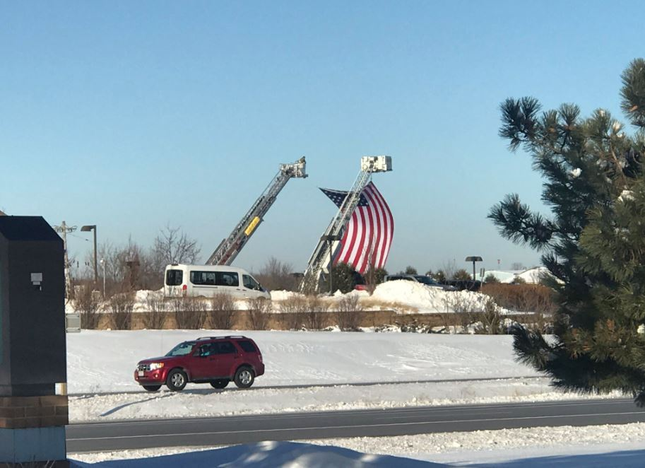 Fire Departments hold up American Flag to honor Officer Matthew Rittner