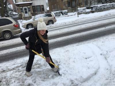 Milwaukee resident with shovel and black jacket digs out from storm