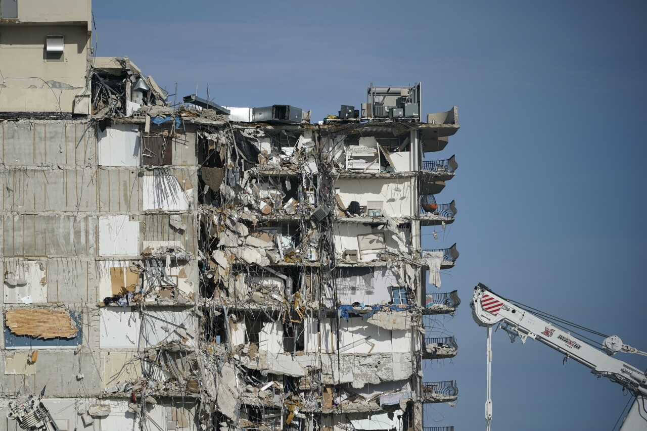 parked crane sits next to still standing portion of Champlain Towers South condo after collapse, July 1, 2021
