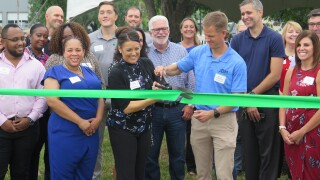 JBM Packaging CEO Marcus Sheanshang, second from right in the front row, cuts a ribbon Aug. 31, 2021, to celebrate the company's expansion into Queensgate. Sheanshange is holding the top of a large pair of scissors and cutting a green ribbon stretched in front of a crowd of supporters.