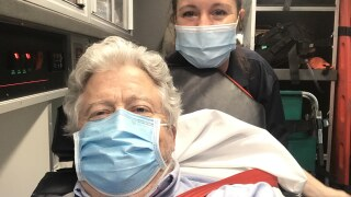 A man with curly gray hair wears a blue medical mask while strapped to a gurney in an ambulance. A paramedic with long dark hair pulled back, also wearing a light blue medical mask and a dark shirt stands behind him. Both are posing for the camera.