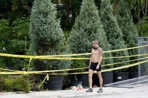 Man walks by scene of Wilton Manors crash where flowers now lay, June 20, 2021