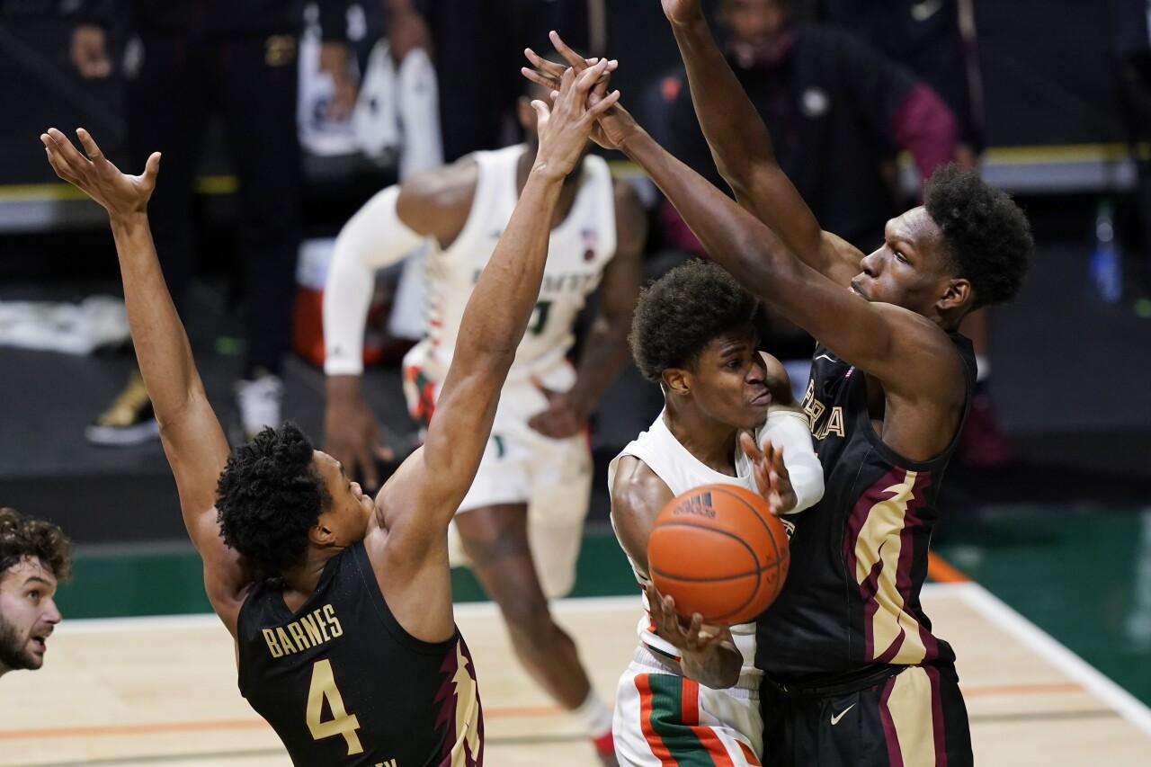 Florida State Seminoles guard Scottie Barnes and center Quincy Ballard stop basket by Miami Hurricanes guard Kameron McGusty, Feb. 24, 2021
