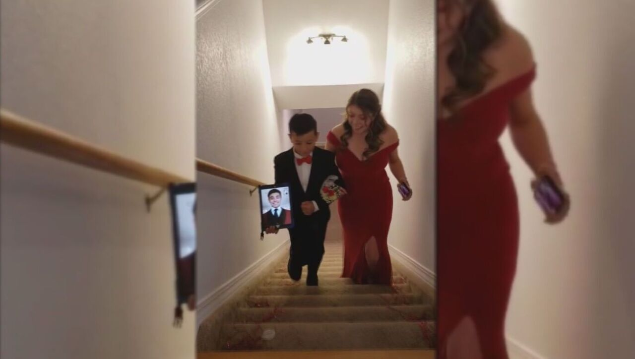 Nine-year-old Tyson Trujillo escorts his sister, 18-year-old Jacelynn Trujillo, to her own 'home prom' while Jacelynn's boyfriend joins remotely.