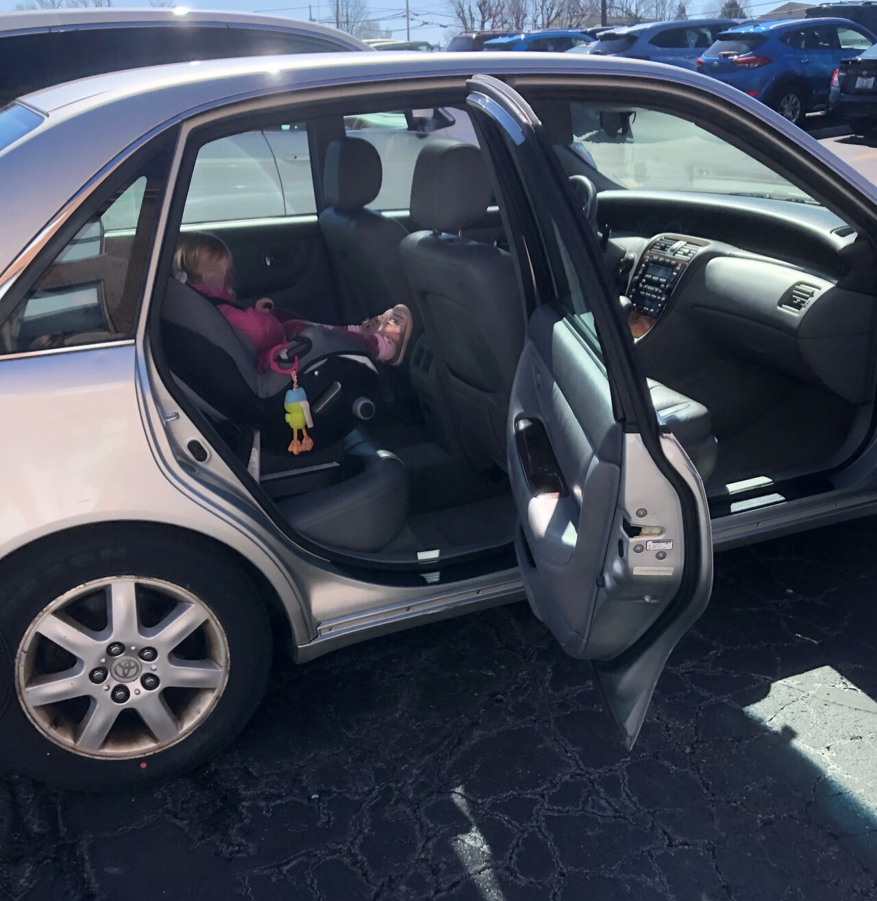 A child sits buckled into a car seat in the back of a 2000 Toyota Avalon. The child's face is blurred for privacy.