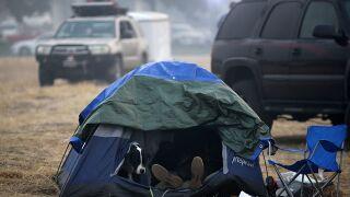 A few hardy California wildfire survivors hunker down for long haul