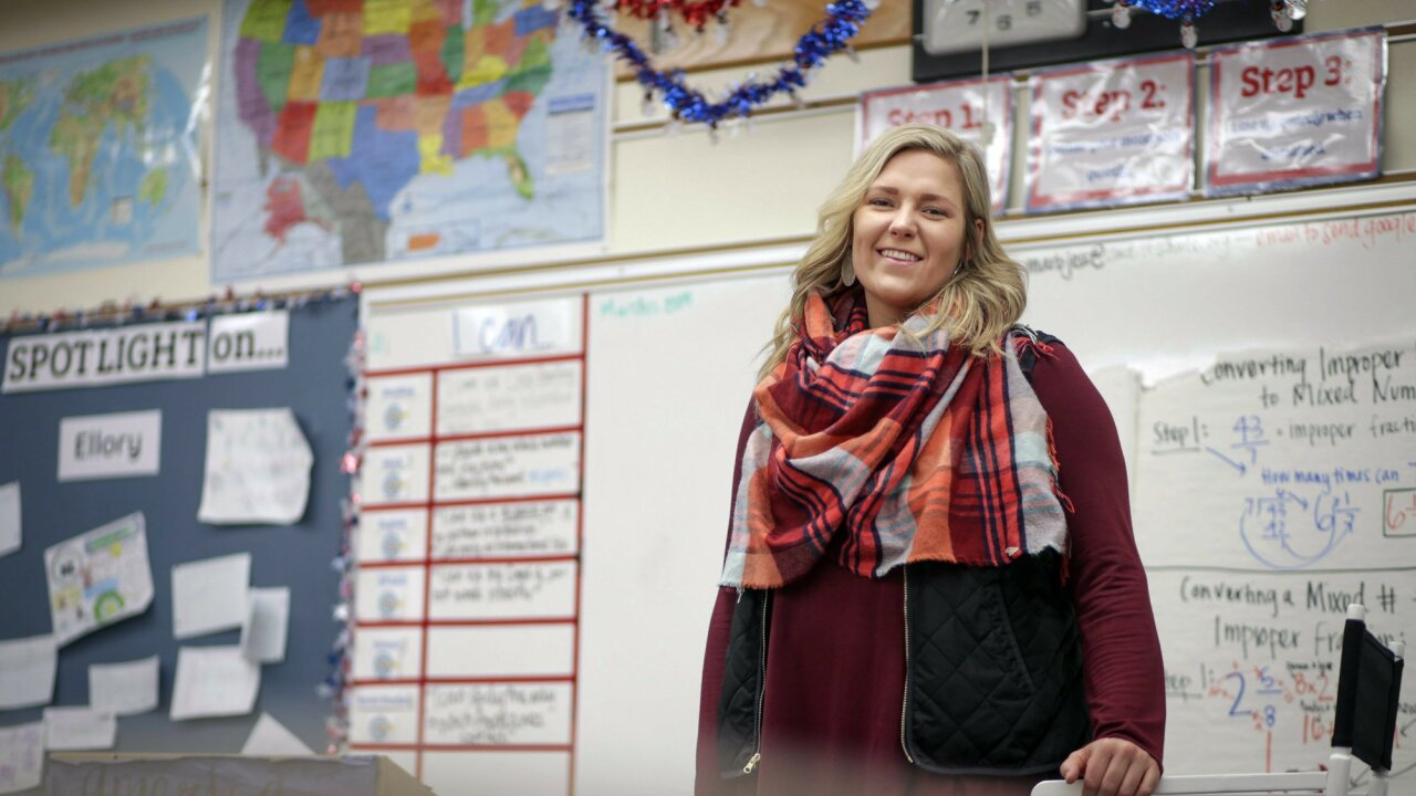 a teacher stands in her classroom