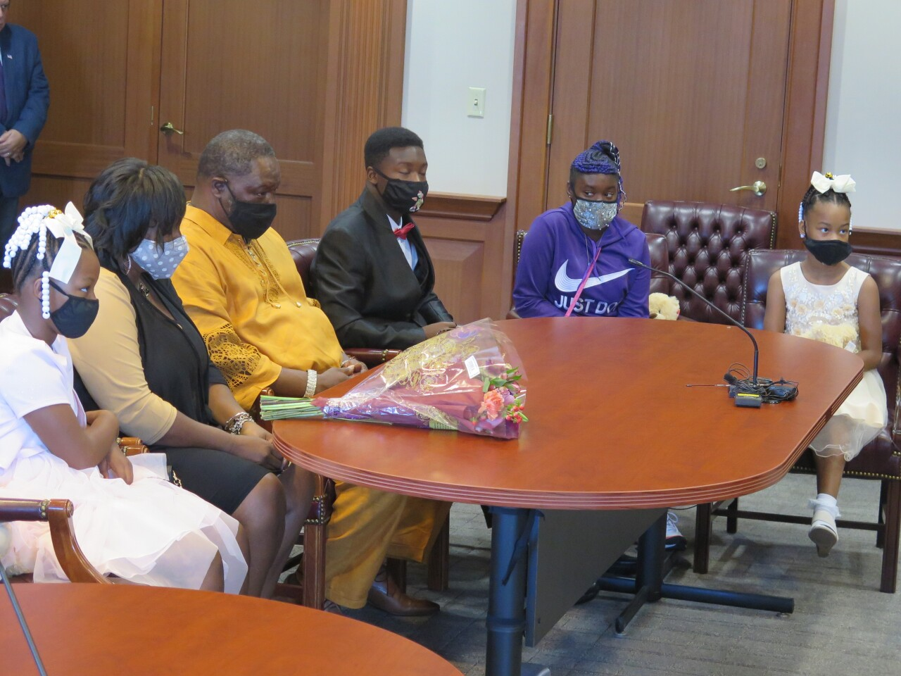 """Karen and Tobias Thompson, second and third from left, in the courtroom with their adoptive children. The younger twin girls are wearing their Easter dresses. The older twin boy is wearing a black jack, red tie and dress shirt, and the older twin girl is wearing a purple Nike sweatshirt that says """"Just do it."""""""