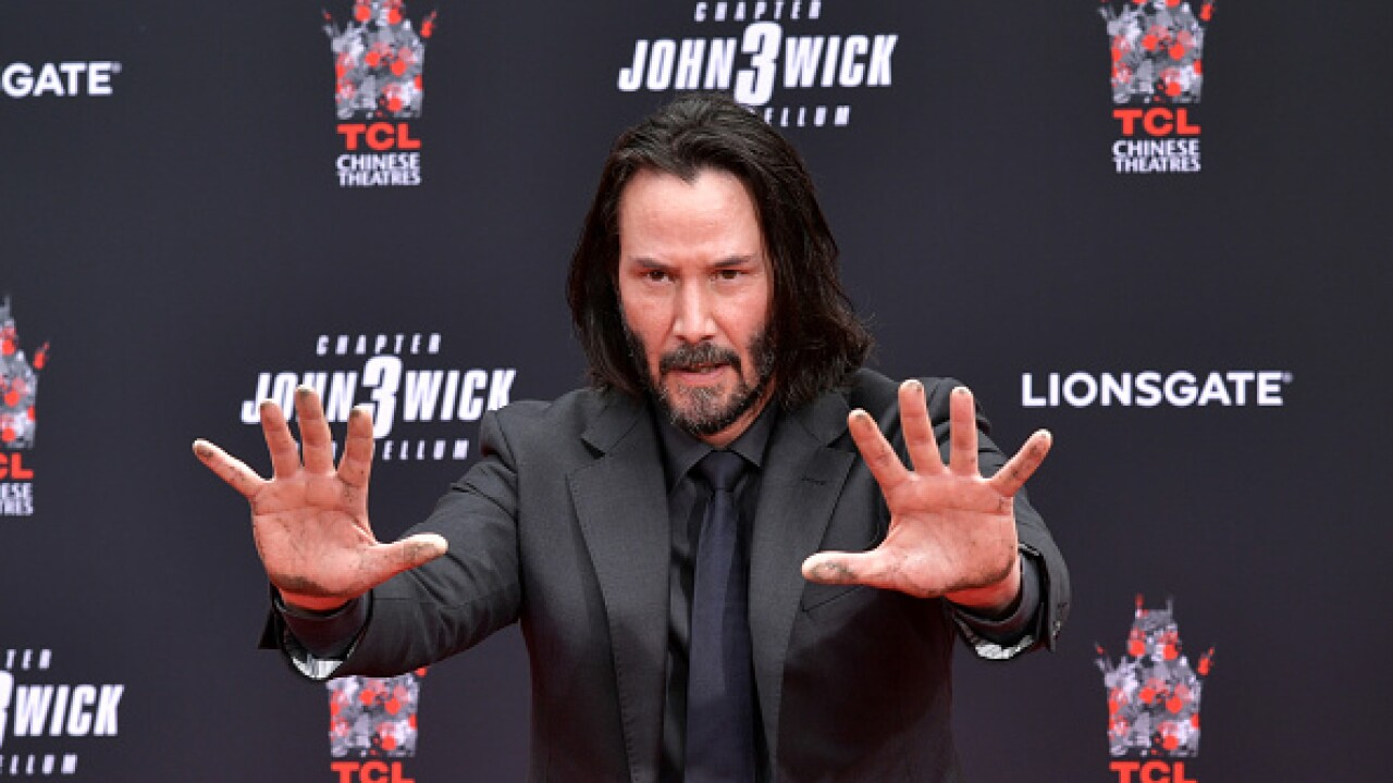 Keanu Reeves Sinks Feet Hands In Cement At Chinese Theatre