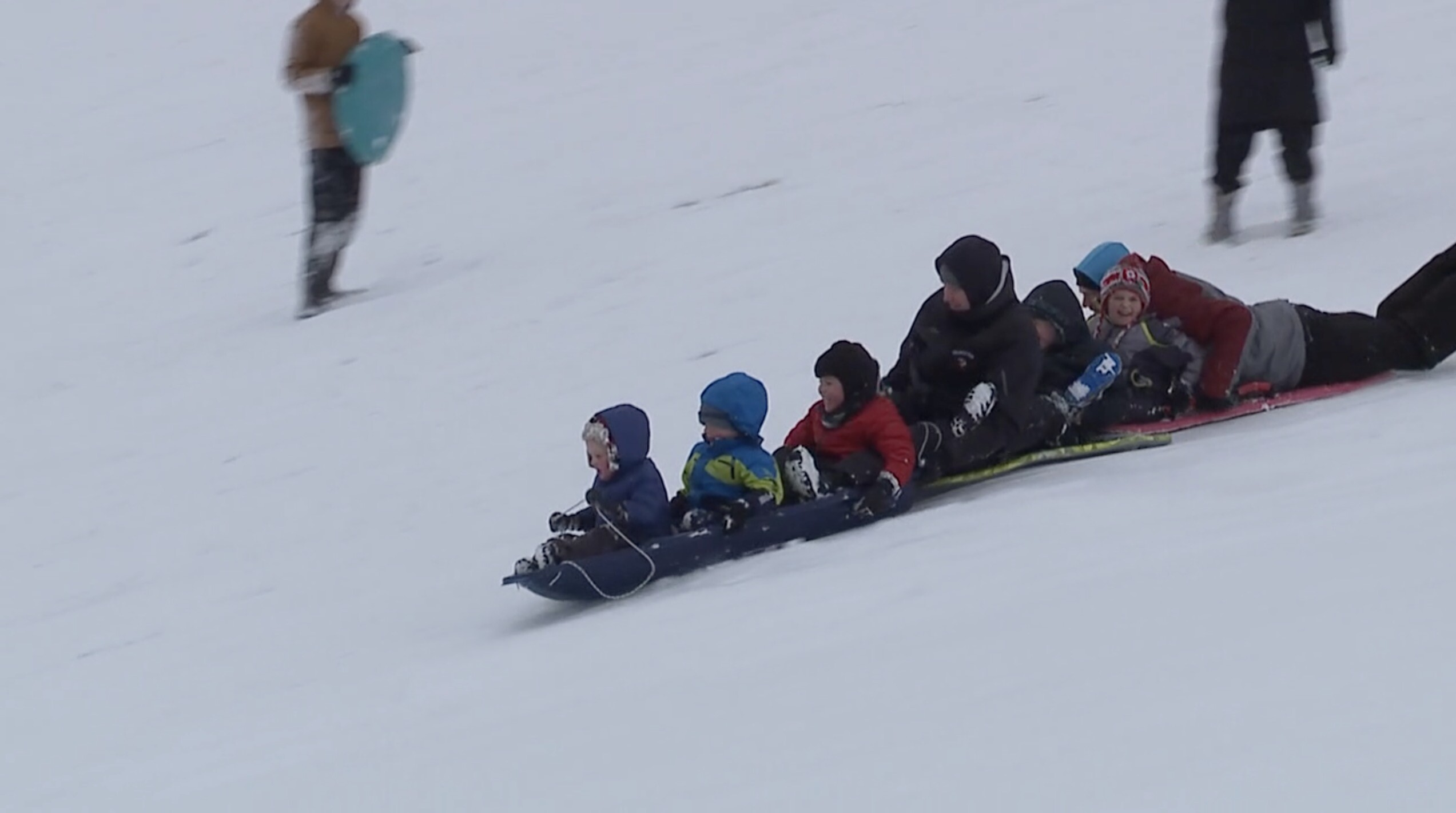 kids sledding snow