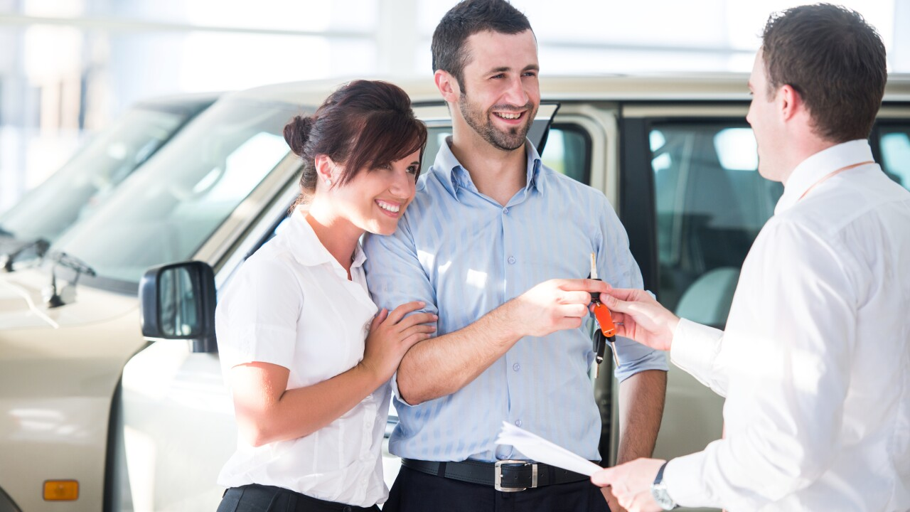 Happy couple getting car keys from a seller