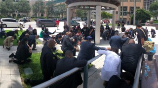 Pastors and law enforcement kneel together in prayer during protest outside Palm Beach County courthouse, June 5, 2020