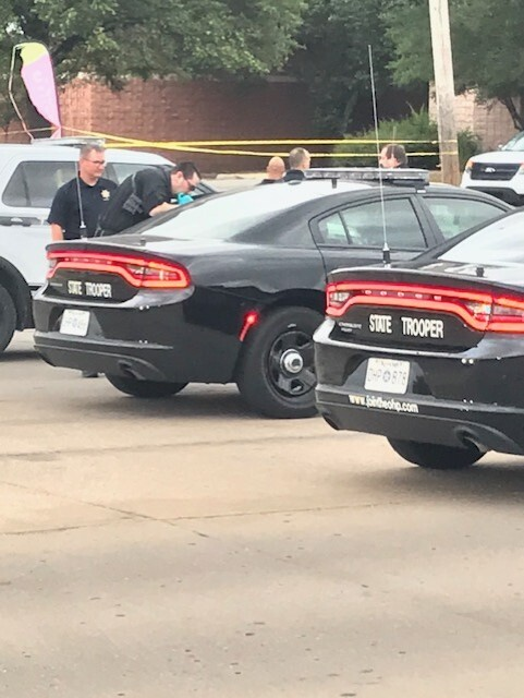 Officers investigating scene after two officers shot during routine traffic stop.