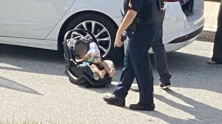 Law enforcement officers tend to a 1-year-old child during a child abuse investigation on Palm Beach on March 1, 2021.jpg