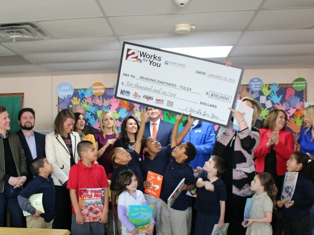 2 Works for You employees give books, present $10,000 check to Reading Partners for TPS students