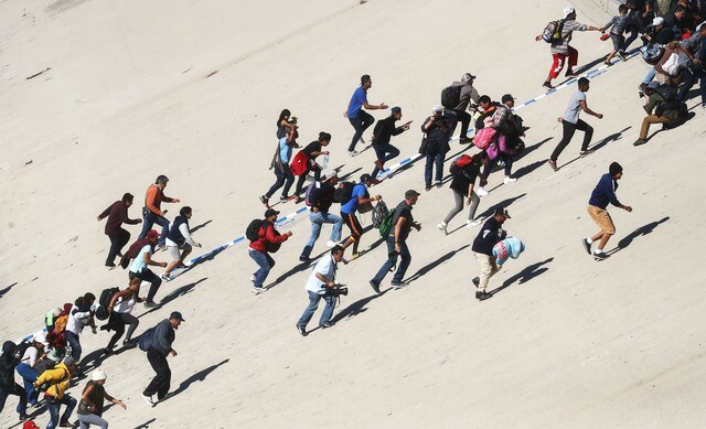 PHOTOS: Migrants rush US/Mexico border to demand asylum