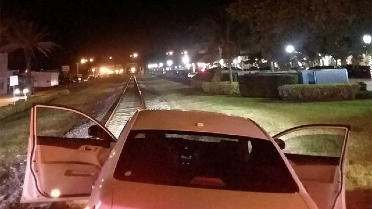 Man rescued from car stuck on train tracks