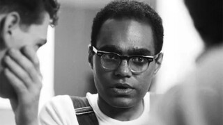 Bob Moses is looking intently at another person in this undated photo taken during his days as a civil rights organizer. He's wearing glasses, a t-shirt and overalls.