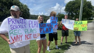 Parents and student-athletes hold signs in protest of sports not being played