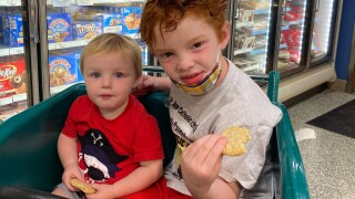 Andrew and Ryan Burke enjoy Publix sugar cookies while sitting in children's shopping cart in May 2021