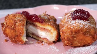 The completed peanut butter and jam fried ice cream, topped with strawberry jam and dusted with powdered sugar.