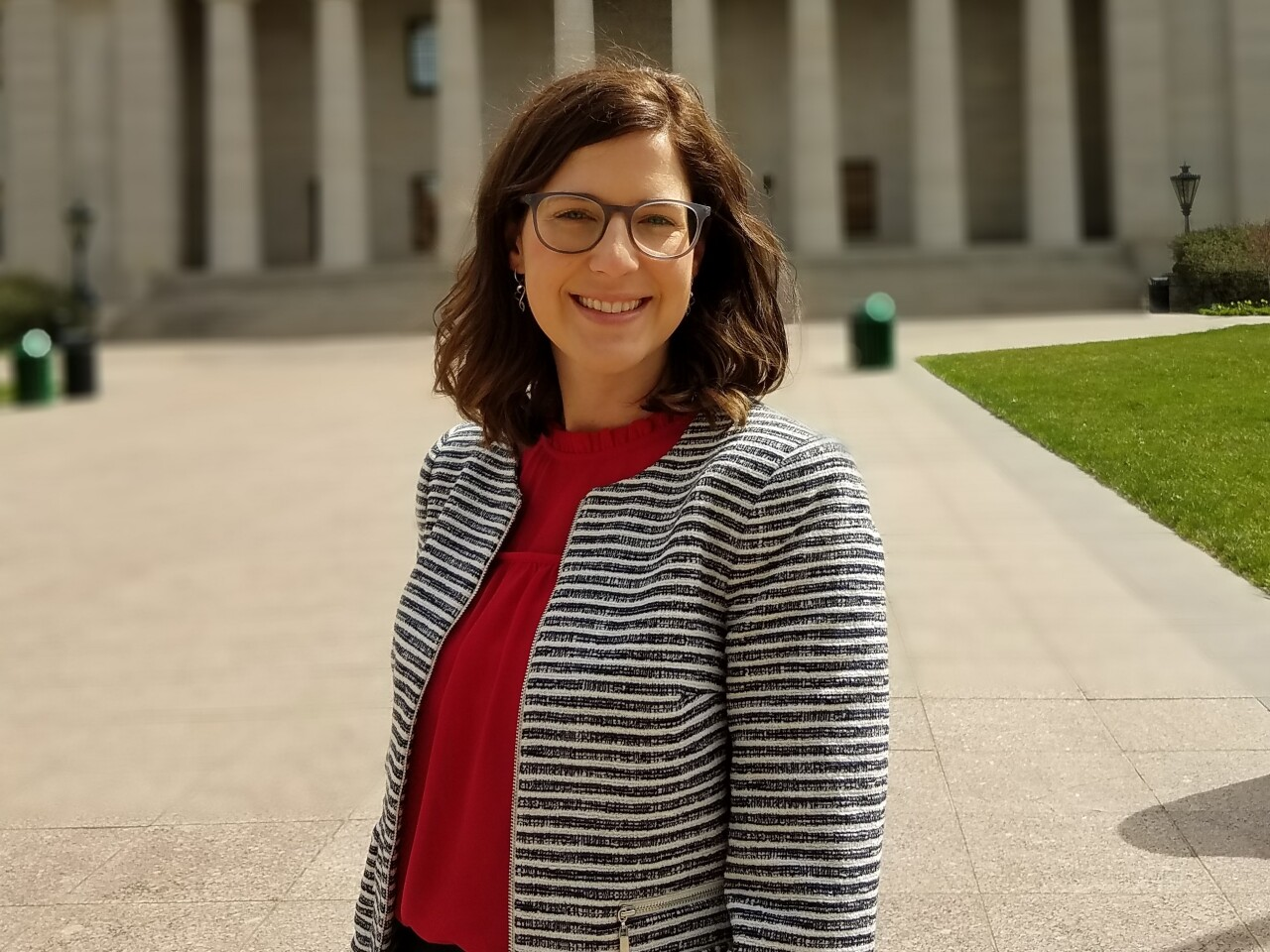 Meg DeBlase stands in front of the Ohio Statehouse building. She has shoulder-length brown hair and is wearing glasses.