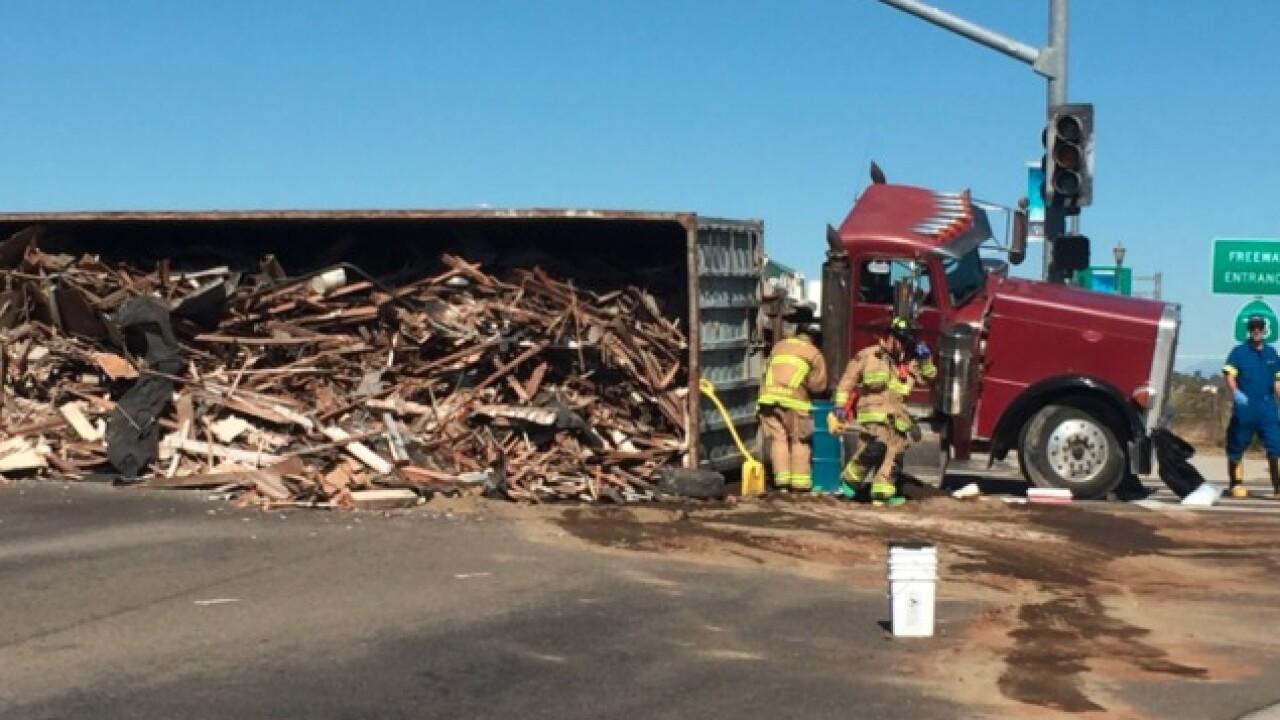 Big rig tips over, spills debris on road
