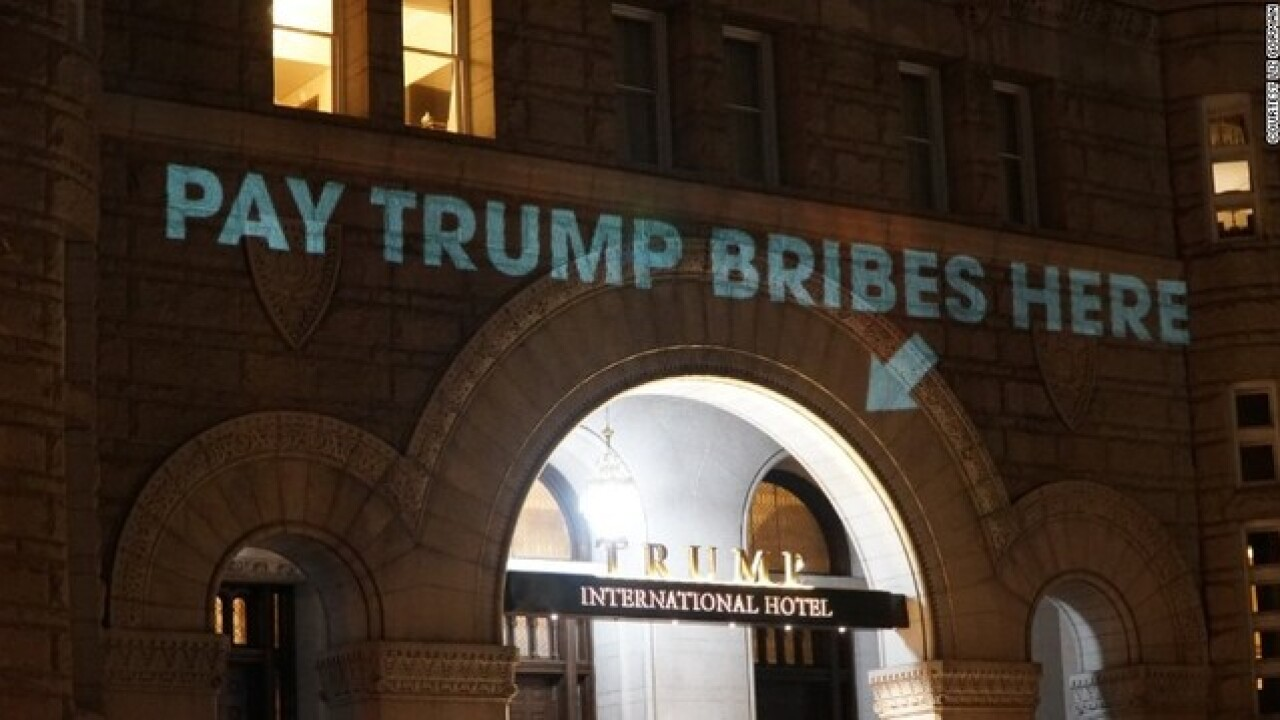 'Pay Trump bribes here' sign projected on hotel