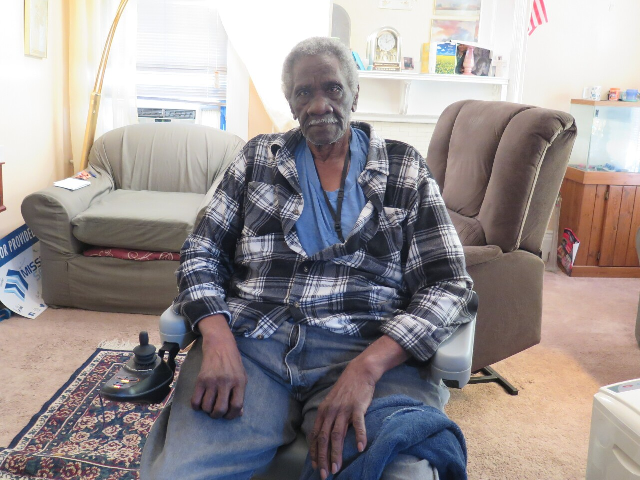 Robert McCrary poses in the living room of his Avondale home. A patterned rug and two chairs are visible behind him.