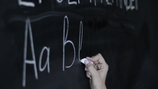 Writing Alphabet on Chalkboard