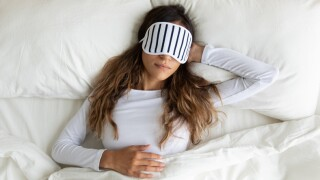 Calm peaceful mixed race young lady wearing sleeping mask, dreaming.