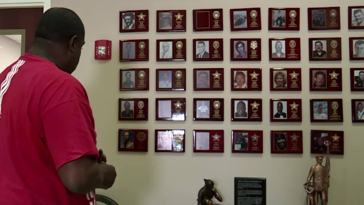 Gregory Allen looks at wall of honor at Palm Beach County Police Benevolent Association