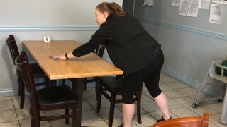 Cheyenne Reed wipes down table and chairs