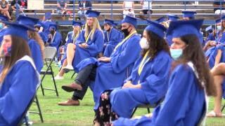 Martin County High School class of 2020 sit in chairs on football field for graduation ceremony