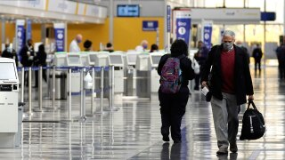 Travelers walk through Terminal 1 at O'Hare International Airport