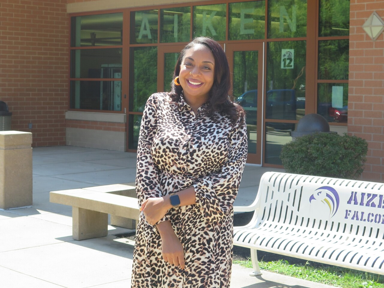 Rachel McMillian smiles in this picture taken outside Aiken High School. She has long dark hair and is wearing a dress with a spotted black and brown print.