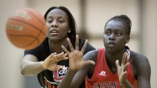 """n this Nov. 28, 2018 photo, Lincoln High School girls basketball coach Dominique Kelley-Johnson, left, guards player Nyayongah Gony during a drill at high school basketball practice in Lincoln, Neb. Administrators say some fans at a recent Fremont High School girls basketball game aimed racist remarks at the visiting Lincoln High School team, leading to a postgame scuffle among fans of the teams. Kelley-Johnson said her team has moved on, """"But it sickens me that how we look still bothers people in 2020."""" (Francis Gardler/Lincoln Journal Star via AP)"""