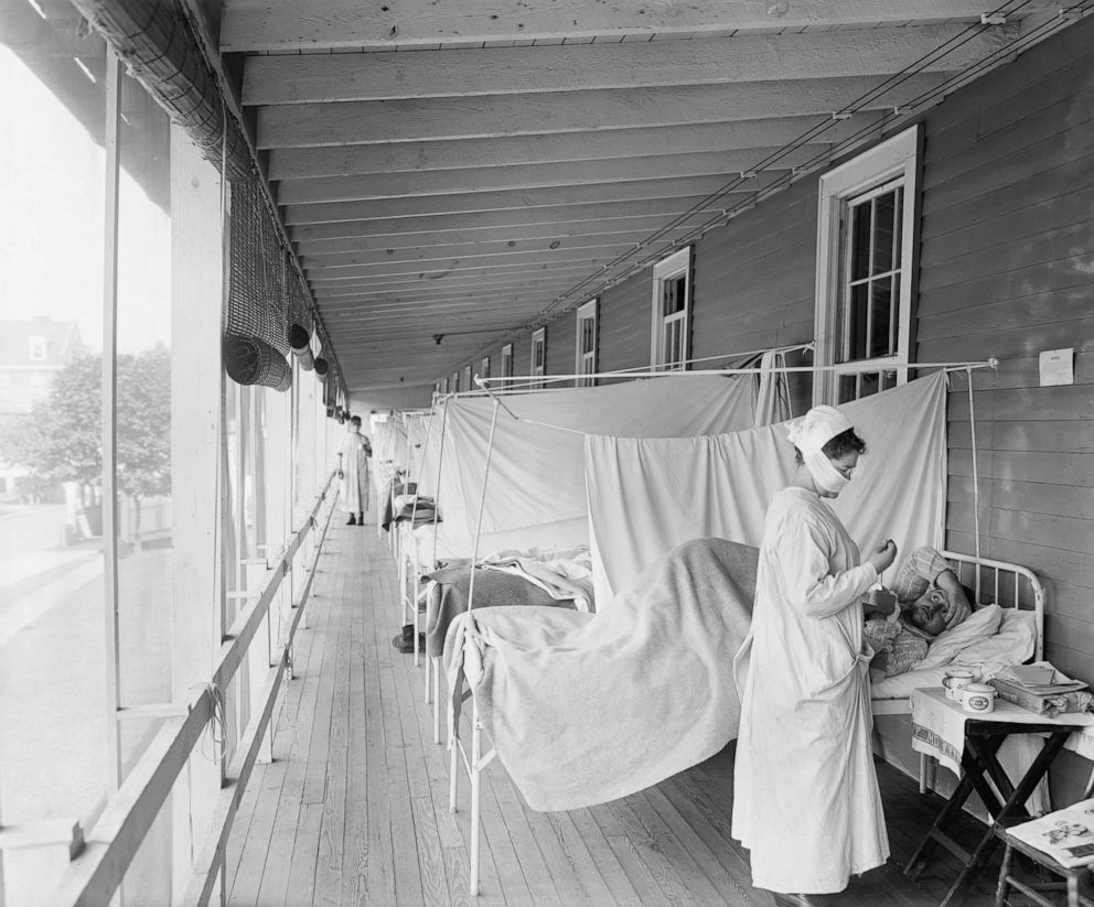 Universal Images Group via Getty Images A masked nurse at the head of a row of beds treats patients during the influenza pandemic at Walter Reed Hospital, in Washington D.C., 1918.