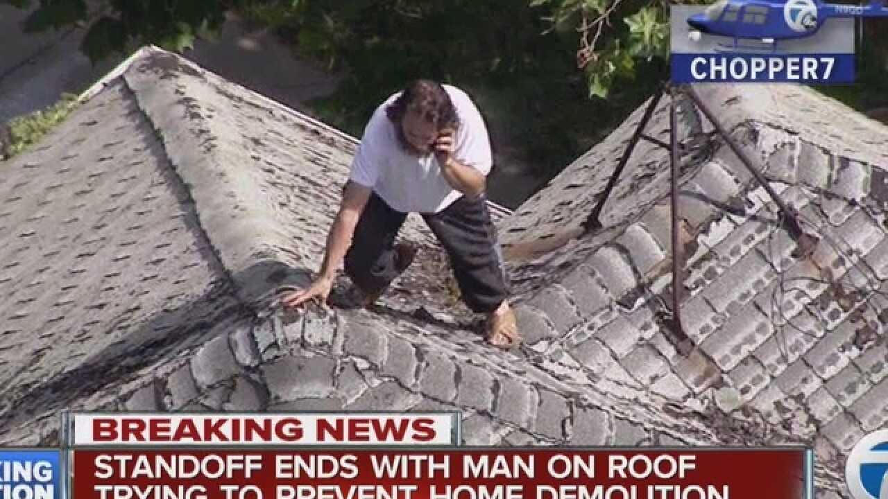 Man sits on roof of house to prevent demolition