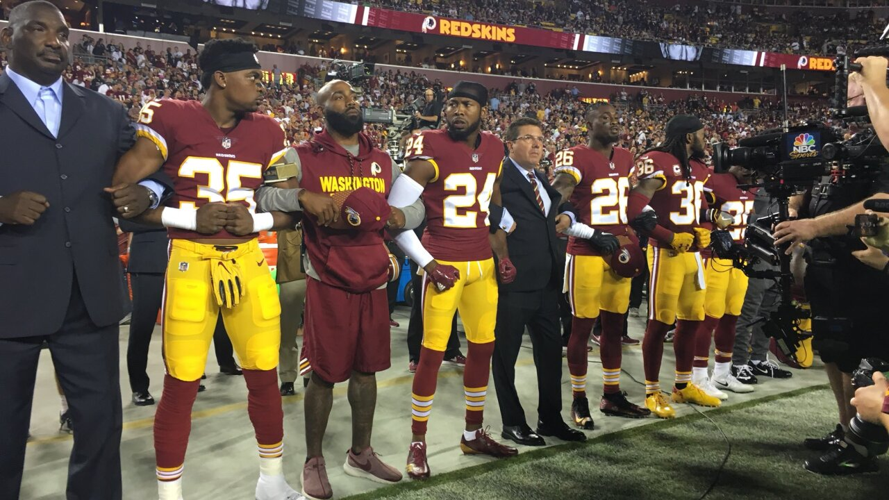 Team owner Daniel Snyder joins arms with Redskins players, some kneeling, during national anthem