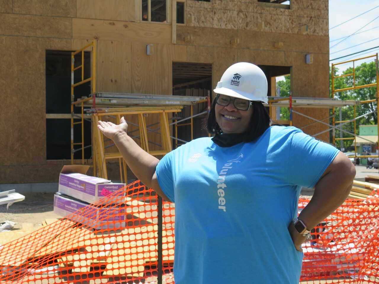 Vera Suggs, wearing a white hardhat and blue t-shirt, smiles and gestures back to her home that is under construction in Bond Hill.