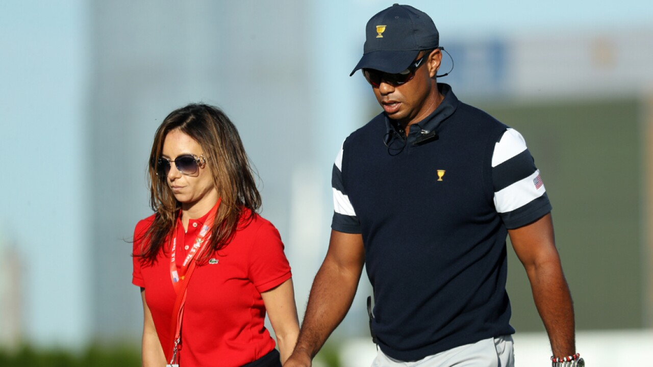 Captain's assistant Tiger Woods of the U.S. Team walks with Erica Herman during Thursday foursome matches of the Presidents Cup at Liberty National Golf Club on September 28, 2017 in Jersey City, New Jersey.