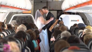 A woman from New Zealand and a man from Australia took their love of aviation (and each other) to new heights by tying the knot 37,000 feet in the air.
