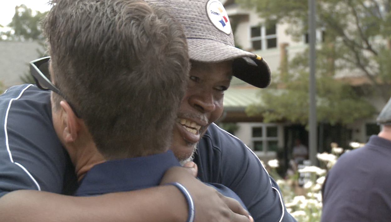 Russell Davis shares a hug at Monday's golf outing