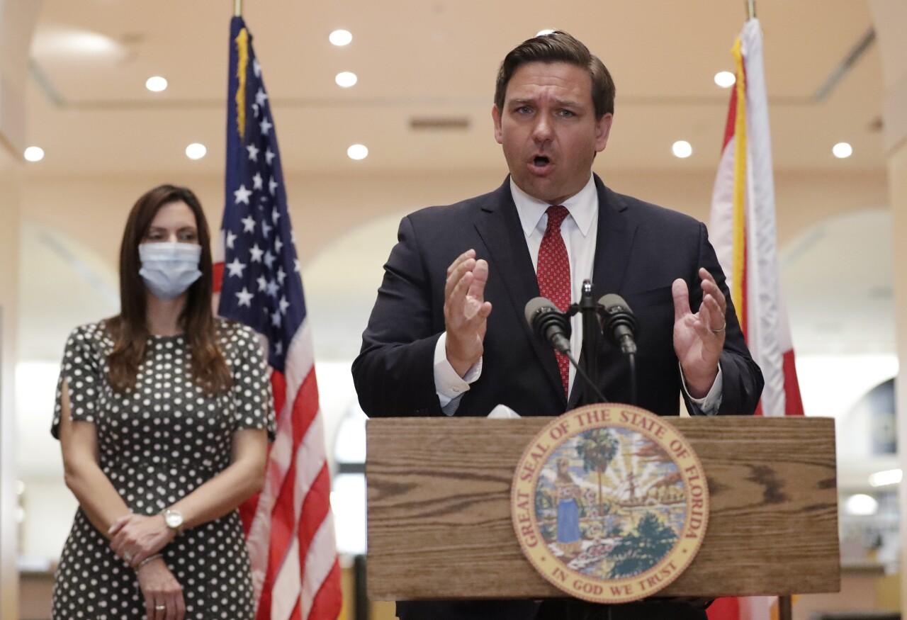 Gov. Ron DeSantis at news conference while Lt. Gov. Jeanette Nunez wears mask