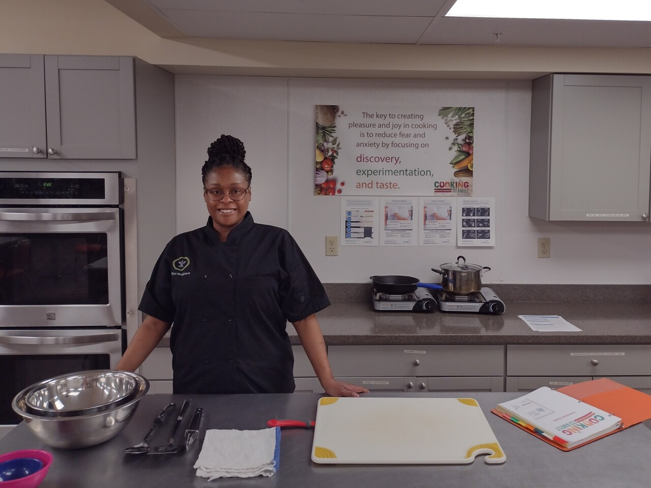 LaToya Bridgeman in the Cooking for the Family Teaching Kitchen at St. Anthony Center in Over-the-Rhine. Bridgeman is smiling and wearing glasses and a black chef coat.