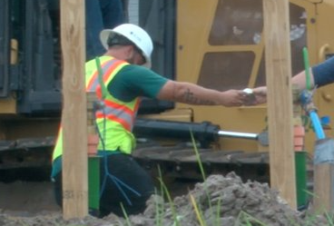 construction workers hand tools to each other .png
