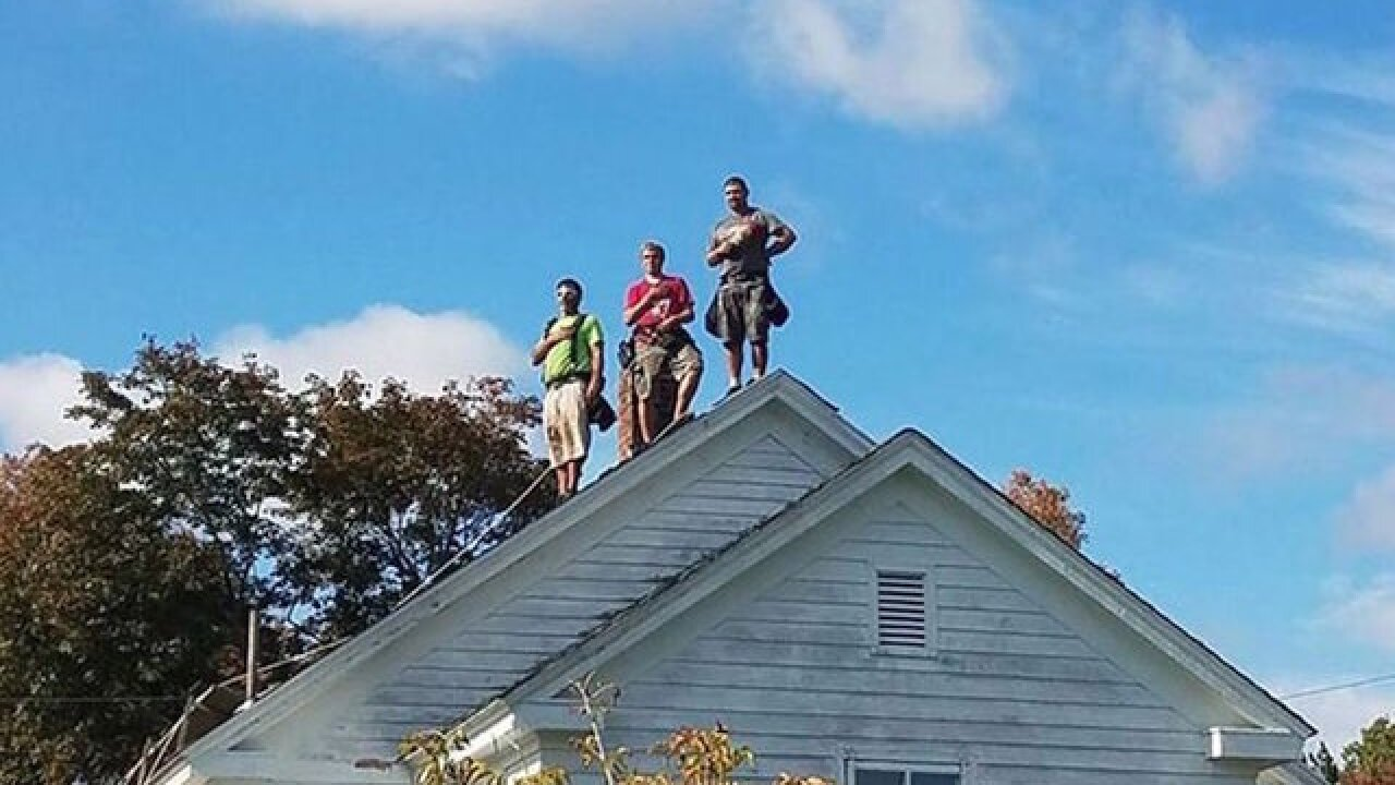3 roofers set hammers aside to stand for National Anthem